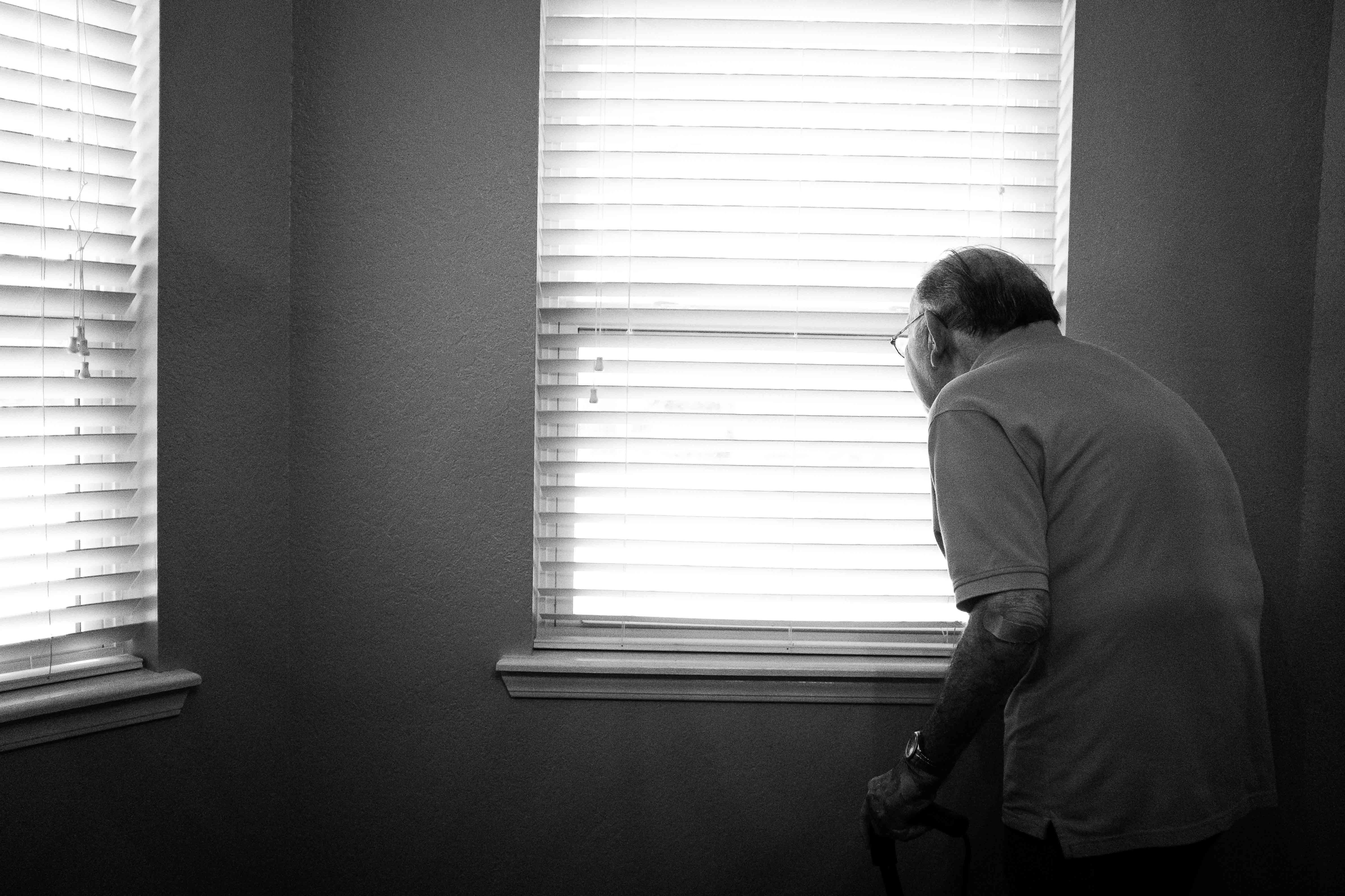 Lonely senior citizen looking out of the window